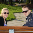 Happy couple sitting in park — Stockfoto