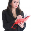 Business woman writing on a notepad — Stok fotoğraf