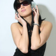Woman with headphones and sunglasses - Stock Photo