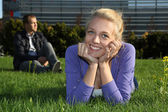 Woman lying and man sitting in park — Stock Photo