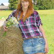 Woman in a field with hay bales — Stock Photo