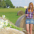 Stock Photo: Woman in a field with hay bales