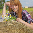 Girl lying on straw bale — Stock Photo