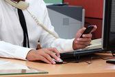 Zakenman met behulp van slimme telefoon tijdens werken — Stockfoto