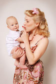 Stylization of happy pin-up girl with baby — Stock Photo