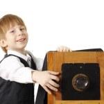 Cheerful boy retro photographer with vintage camera in studio — Stock Photo #12128379