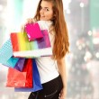 Shopping teen girl smiling with bags in christmas store — Stock Photo