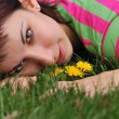 Royalty-Free Stock Photo: Woman with dandelion lying on green grass in spring park