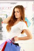 Shopping teen girl smiling holding bags — Stock Photo
