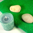 Candle and stones on green towel — Stock Photo #12045547