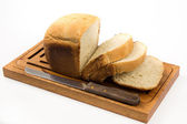 Sliced ​​white bread on the home board with knife — Stock Photo