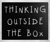 Thinking outside the box phrase, handwritten with white chalk on — Stock Photo