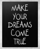 """Make your dreams come true"" handwritten with white chalk on a b — Stock Photo"