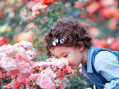 Baby girl smelling pink roses — Stock Photo