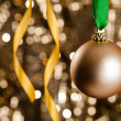 Single golden Christmas bauble in front of a gold glitter backgr - Stock Photo