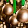 Three golden Christmas baubles in front of a gold glitter backgr - Stock Photo