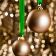 Two gold Christmas baubles in front of a gold glitter background - Stock Photo