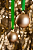 Two gold Christmas baubles in front of a gold glitter background — Stock Photo