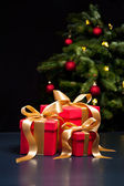 Three presents with gold ribbon — Stock Photo