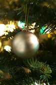 Decorative gold bauble in a Christmas tree — Stock Photo