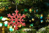 Red artificial snow flake in a christmas tree — Stock Photo