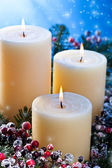 Three candles with snowfall — Stock Photo
