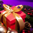 Red present box in a purple Christmas setting — Stock Photo
