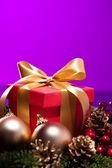 Röda nuvarande rutan i en lila jul miljö — Stockfoto