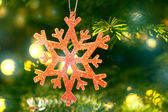 Red snow flake in a christmas tree with neon colors — Stock Photo