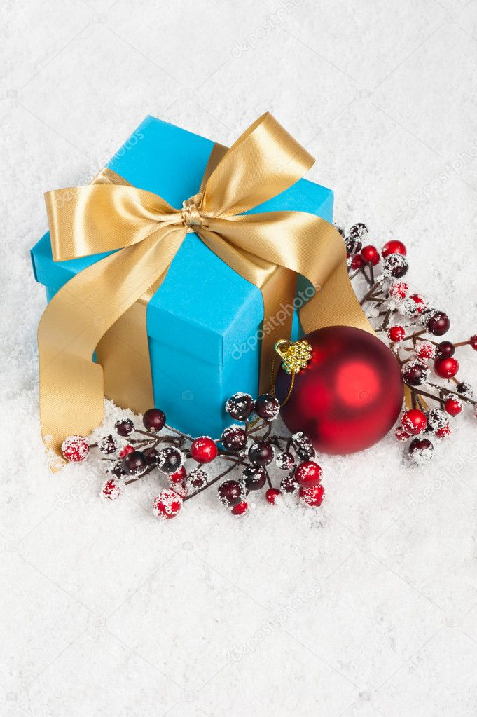 Blue present with gold ribbon and Christmas decoration — Stock Photo #11756565