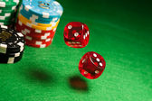 Rolling red dice on a casino table — Stock Photo