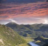 Cloudy sunset sky and river in the mountain cross the valley, mo — Stock Photo