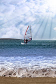 Windsurfer in a storm with rays of sunshine — Stock Photo