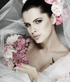 An elegant sexual brunette is in a wedding dress, decorated pink colors — Stock Photo