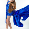Beautiful girl, dancing in the blown about fabric on a light background - Stockfoto