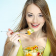 Portrait of a pretty young woman eating fruit salad isolated on a white background — Stock Photo