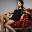 Sexual girl with dark hairs, sitting on a red arm-chair — Stock Photo