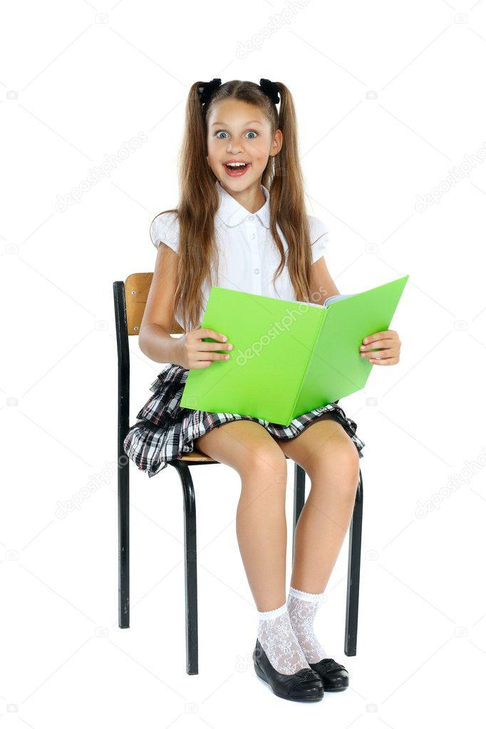 une petite fille est dans une forme d cole qui est assis sur une chaise et lit un livre. Black Bedroom Furniture Sets. Home Design Ideas