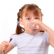 Little girl with a tooth brush drinks water from the glass — Stock Photo #10741019