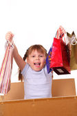 Happy little girl in a cardboard box with purchases — Stock Photo