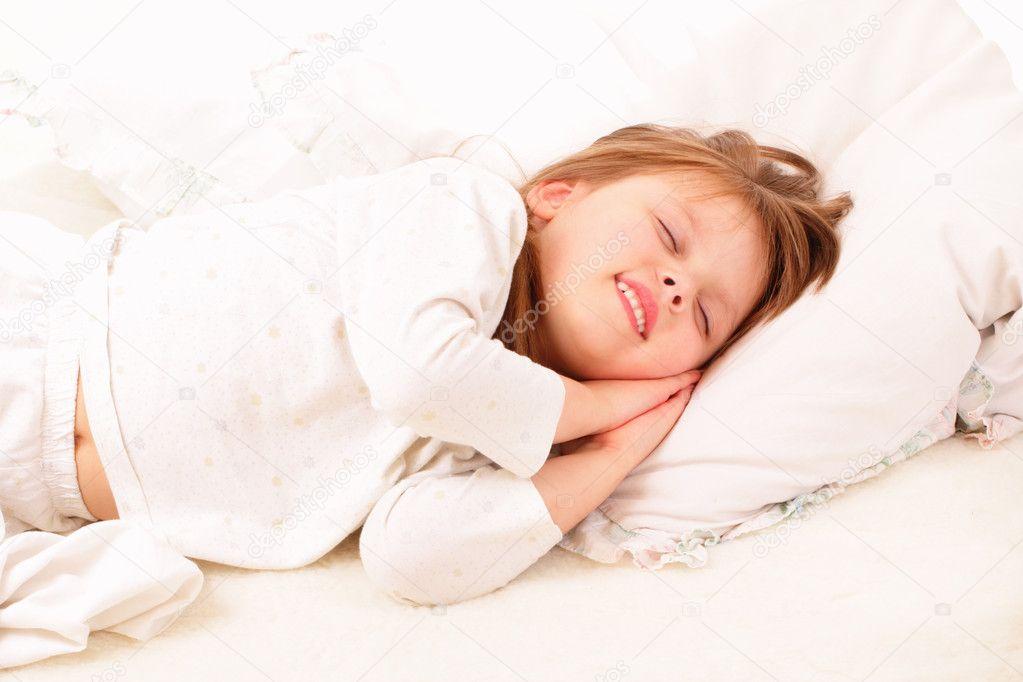 heureuse petite fille dort dans son lit photo 10822860. Black Bedroom Furniture Sets. Home Design Ideas