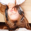 Pretty little girl upside down with headphones — Stock Photo
