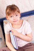 Beautiful little girl sitting with book — Stok fotoğraf