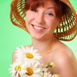 Smiling young girl in the hat with chamomile flowers — Stock Photo