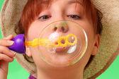 Slarvig ung flicka i en hatt blåser såpbubblor — Stockfoto