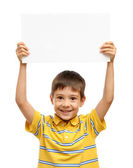 Happy child holding empty poster isolated on white background — Stock Photo