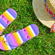 Colourful flip flops and a straw hat - Stockfoto