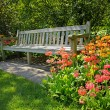 Wooden bench and bright blooming flowers — Stock Photo #11378063