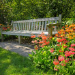 Foto de Stock  : Wooden bench and bright blooming flowers