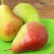 Three ripe juicy pear on a wooden table - Stock Photo